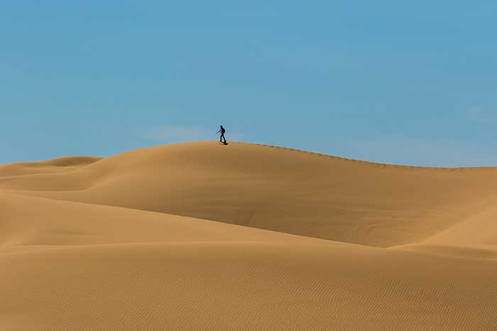 person walking in the desert